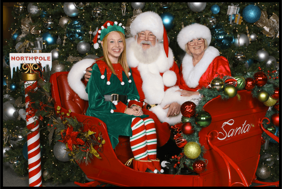 Santa and Ms. Claus with cute little elf sitting on sleigh. Santa for hire Houston